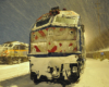 A closeup shot of a train parked, covered in snow.