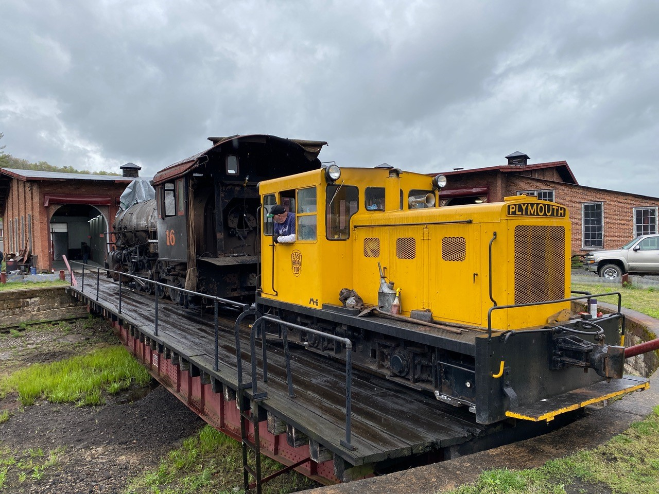 A yellow Plymouth diesel locomotive pauses on a turntable waiting to shove an East Broad Top steam locomotive into a shop.