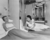 A couple of women laying in their beds talking through an open partition