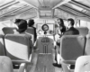 A black and white photo of people sitting inside a train