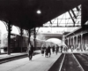 A black and white photo of people walking through a train station