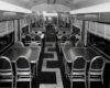 A black and white photo of the inside of an empty lounge diner train