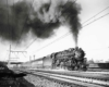 A black and white photo of a train with big black smoke coming out of it