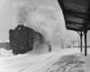 a steam engine passenger train at a passenger depot on a snowy day