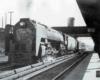 a steam locomotive passenger train at a depot