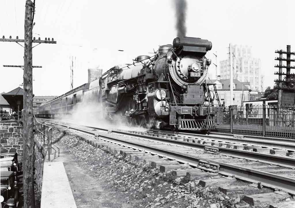 A black and white photo of a train leaving a station