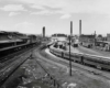 A black and white distant shot of a train station and locomotives in a rail yard
