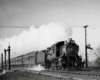 A black and white photo of a train with white smoke coming out of its chimney