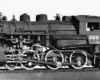 A close up black and white photo of a locomotive