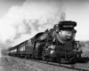 A black and white photo of a train coming down the tracks with white smoke coming out of its chimney
