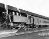 A black and white photo of a train outside a station