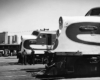 A black and white profile view of two trains with workers nearby