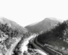 A black and white birds eye view of a train moving through mountains