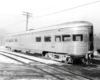 A black and white photo of a tavern lounge car sitting on the tracks