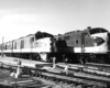 A back and white photo of two locomotives sitting on the tracks