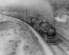 A black and white photo of a train turning a corner