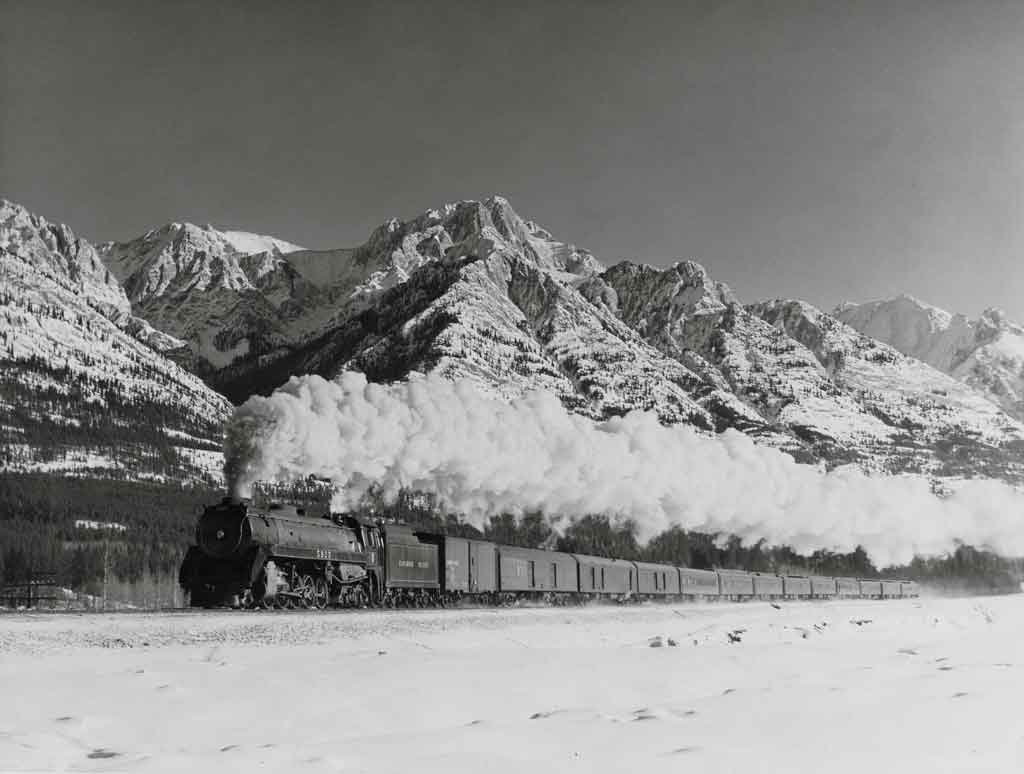 Steam powered passenger train in front of snow capped mountains