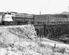 Diesel locomotive on steel bridge with four passenger cars