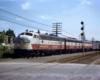 Three diesel locomotives pull passenger train by signal