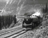 Streamlined steam locomotive on passenger train in wooded mountains
