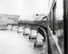 Steam powered passenger train on curved bridge over water