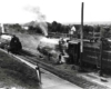 Men work on a steam locomotive while a second approaches