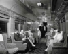 A black and white photo of passengers sitting in a lounge car