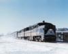 A locomotive travelling through a snowy city