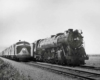 A black and white photo of two locomotives travelling side by side