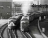 A black and white photo of two locomotives turning a corner at the same time