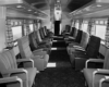 A black and white picture of empty seats inside a train