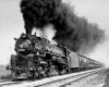 A black and white photo of a train with black smoke coming out of its chimney