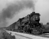 A black and white photo of a locomotive with smoke coming out of its chimney