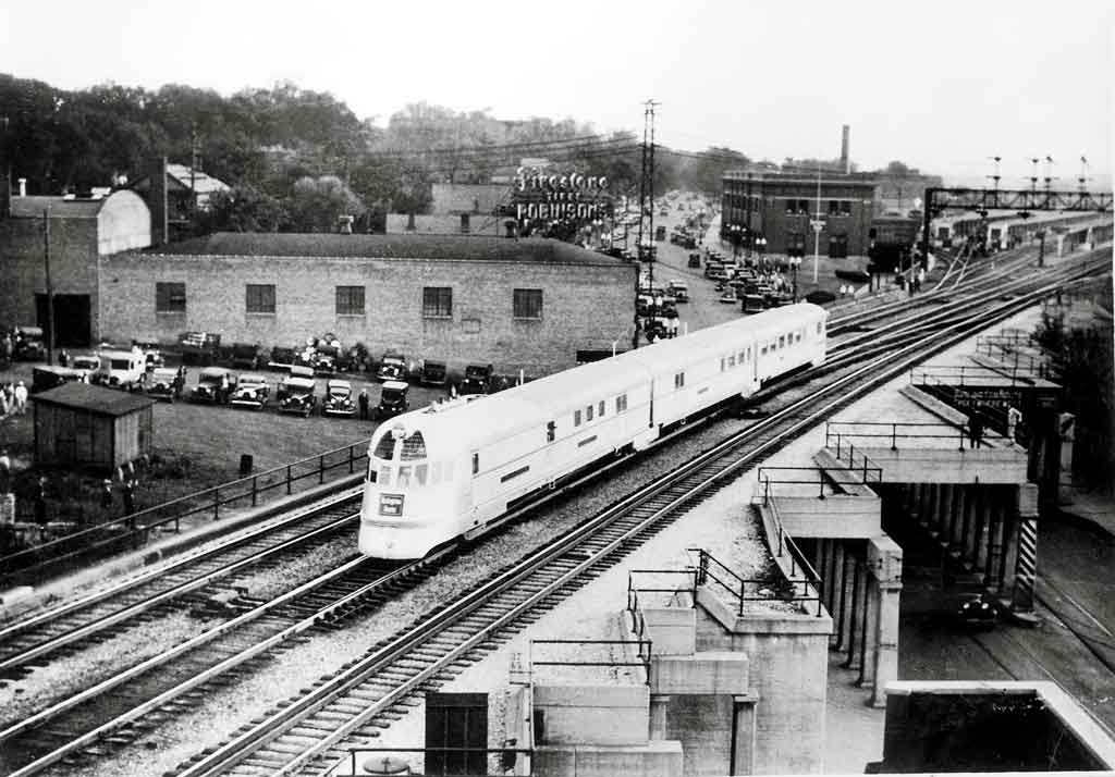 A black and white photo of a locomotive passing over a bridge