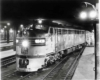 A close up black and white photo of a parked train in the dark with its lights on