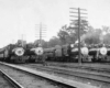 A black and white photo of five trains sitting in a rail yard