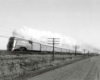 A black and white photo of a train traveling through a rural area