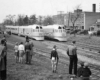 A black and white photo of a group of people watching two passenger trains go by