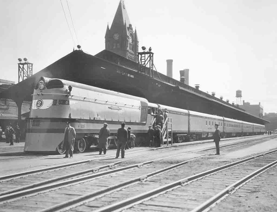 A black and white photo of passengers loading a train