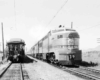 A black and white photo of two trains traveling side by side