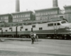 A black and white photo of a couple people standing outside a locomotive