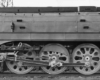 A black and white close up photo of the wheels of a train