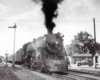 A black and white photo of a locomotive with black smoke coming out of its chimney