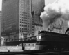A black and white photo of a locomotive with white smoke coming out of its chimney while passing by a city