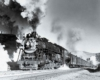 A close up black and white photo of a locomotive with smoke coming out of its chimney