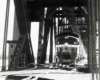 A close up black and white photo of a train coming through a bridge