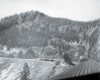 A black and white photo taken from the top of a locomotive looking back at the train and the mountains