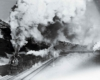 A black and white photo of a train with big white smoke coming out of its chimney