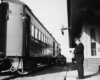 A black and white photo of the train conductor standing outside at the train station