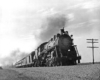 Steam locomotive with four passenger cars at speed